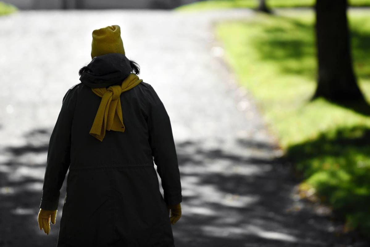 Nainen kävelee puistossa.