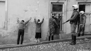 mustavalkoinen kuva, jossa sotilaat tutkivat selinolevia seinään nojaavia aikuisia