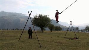 mies harjoittelee nuorallatanssimista ja toinen mies katsoo