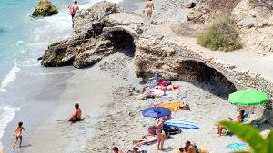 Turisteja ottamassa aurinkoa ja viettämässä aikaa rannalla.