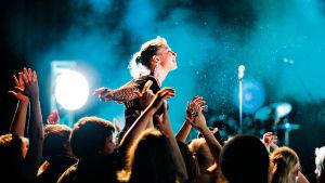 Yleisö taputtaa käsiään rock-konsertissa, yksi tyttö muiden yläpuolella.