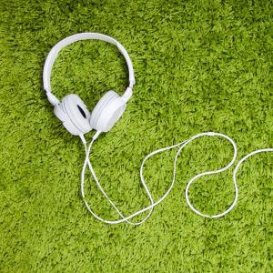 Kuulokkeet ja puhelin vihreällä matolla