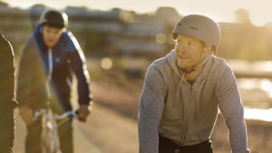 kolme polkupyöräilijää satamassa aamuauringossa, mies etualalla katsoo sivulle ja hymyilee