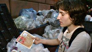 Nuori mies etsii kaupan pois heittämää ruokaa jäteastiasta