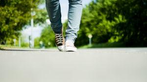 Miehen jalat joissa tenarrit asfaltilla