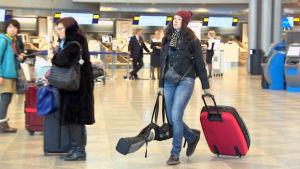 Nainen kulkee lentokentällä suksipussin ja matkalaukun kanssa.