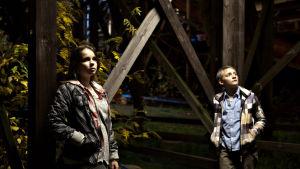 tyttö ja poika iltavalaistuksessa Vuoristoradan rakenteiden alapuolella