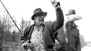 Urho Kekkonen painii kalan kanssa hämmästynyt ilme kasvoillaan.