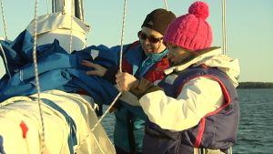 kaksi naista taittelee purjetta