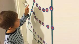 Poika katselee oveen teipattua kuusen muotoista joulukalenteria