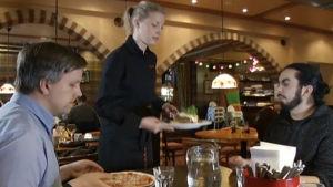 Kaksi miestä ja tarjoilija ravintolassa