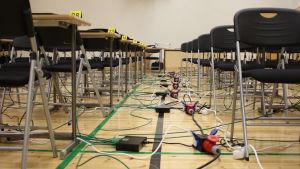 Koulun juhlasali, jossa puolpetteja ja piuhoja lattialla