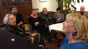 Marjukka Riihimäki laulattaa Muistaakseni laulan -kuoroa dementiakoti Wilhelmiinassa