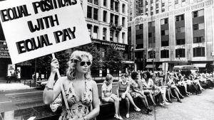 Mielenosoittaja pitelee palkkatasa-arvoa vaativaa kylttiä.