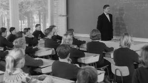 Opettaja  ja oppilaita koululuokassa