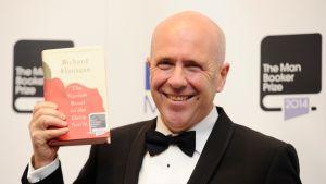 """Australilainen kirjailija Richard Flanagan  pitää käsissään Booker Prizen voittanutta kirjaansa """"The Narrow Road to the Deep North"""""""