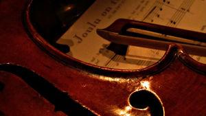 Kuvassa viulu, jousi ja joulunuotti.