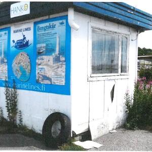En kioskaktig vit liten byggnad med platt tak i dåligt skick, reklamplanscher på väggen.