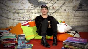 En kille sitter bland kuddar och böcker.