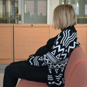 Gravid kvinna sitter vänd i profil mot kameran på en soffa
