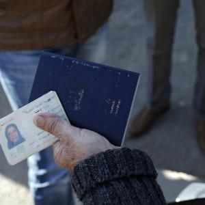 Syrisk kvinna visar id-kort vid gränsen mot Turkiet.