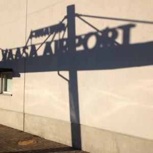 Skuggbild vid Vasa flygplats, i fotot ser man skuggan av flygplatsskylten mot terminalväggen.