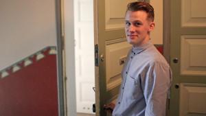 Victor Penttinen som bostadssparar håller upp dörren till sin hyresbostad.