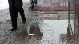 Folk vandrar på slaskig gata