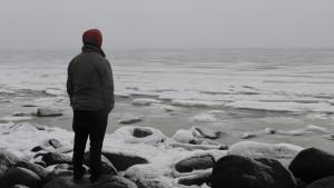 En kille som står och tittar ut över havet.