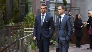 Huvudpersonerna från Suits, iklädda kostymer.