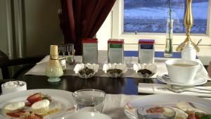 På ett cafébord finns olika tesorter och en kopp te med efterrätt.