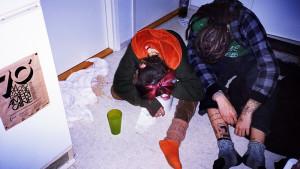 Två personer som ligger på ett golv, omgivna av spyor och annat sunkigt.