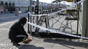 En man lägger ner blommor utanför den restaurang i Göteborg där en gängrelaterad dödsskjutning ägde rum 18.3.2015
