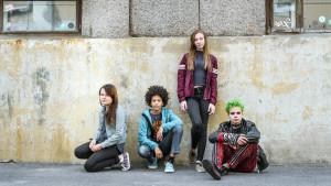 ungdomar sitter vid husvägg