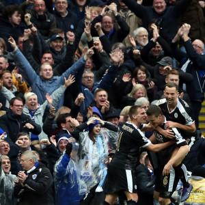 Supportrar jublar bakom Leicesters spelare.