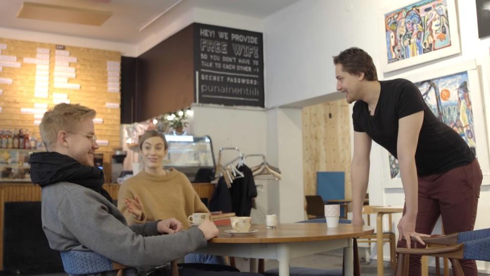 Jevgeni Särki juttelee ihmisille kahvilassa.