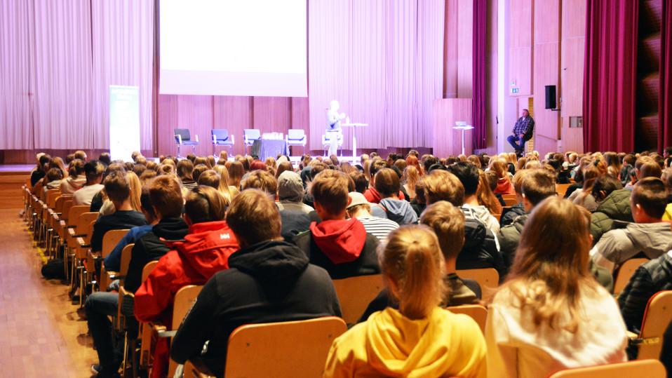 Kuvassa koululaisia istumassa salissa