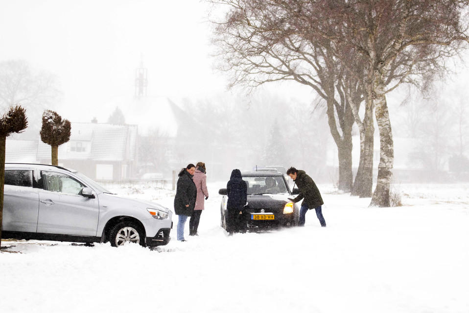 People are pushing cars stuck in the snow in Holland.