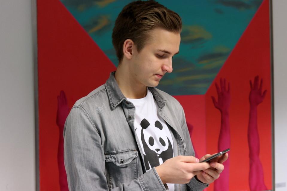 Nuori poika  Mikael Lumme katsoo kännykkäänsä.