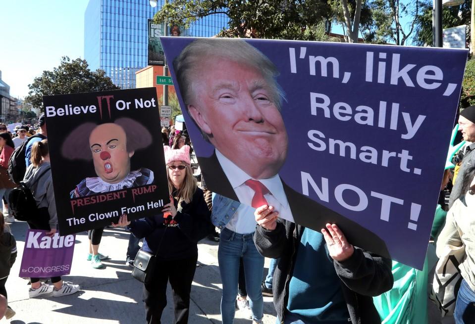 Mielenosoittajat pitelevät presidentti Donald Trumpia pilkkaavia kylttejä mielenosoituksessa Los Angelesissa Kaliforniassa.