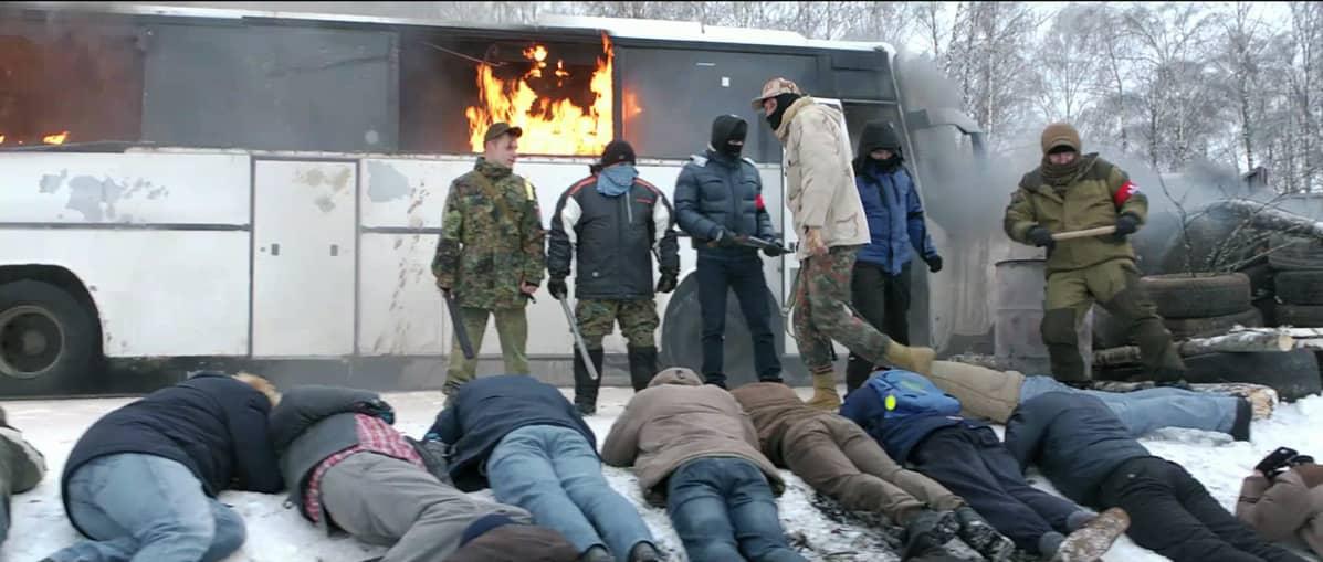 Ihmisiä maassa makaamassa, taustalla palava bussi.