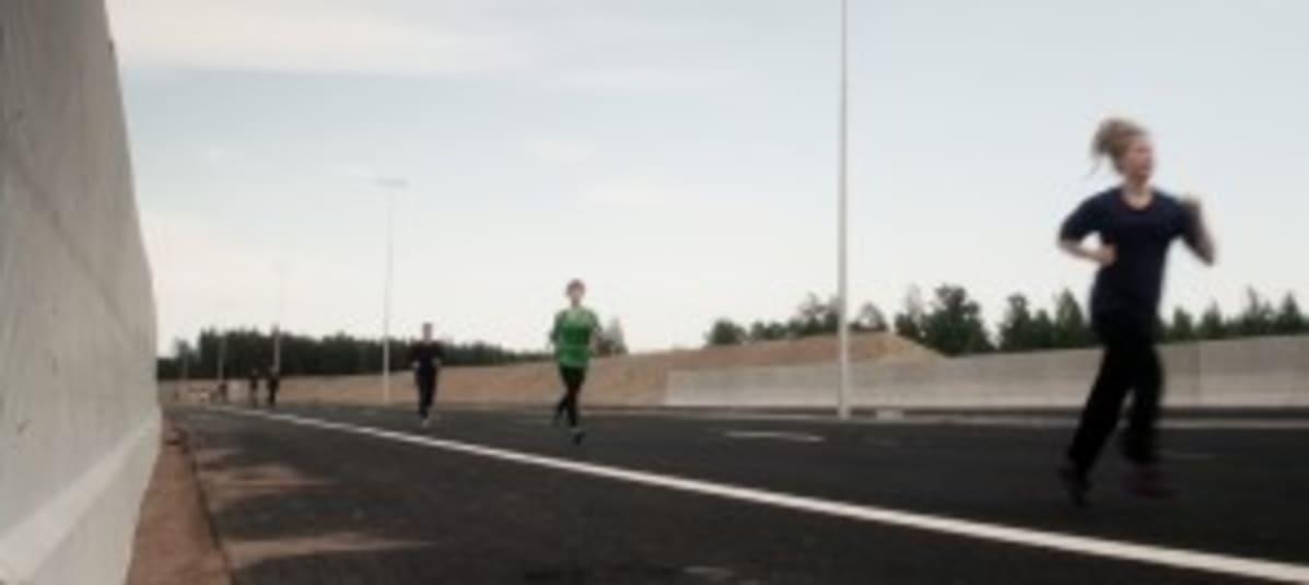 Ihmisiä juoksee moottoritiellä