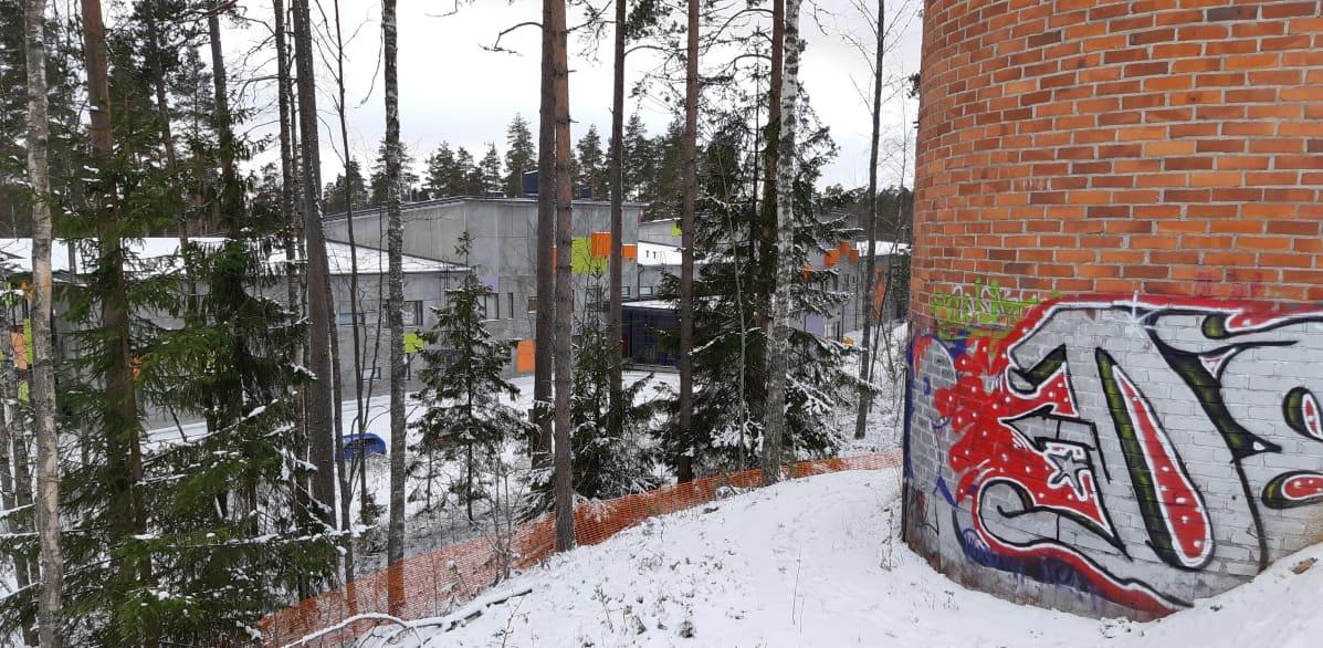 Koulurakennus mäen alla.