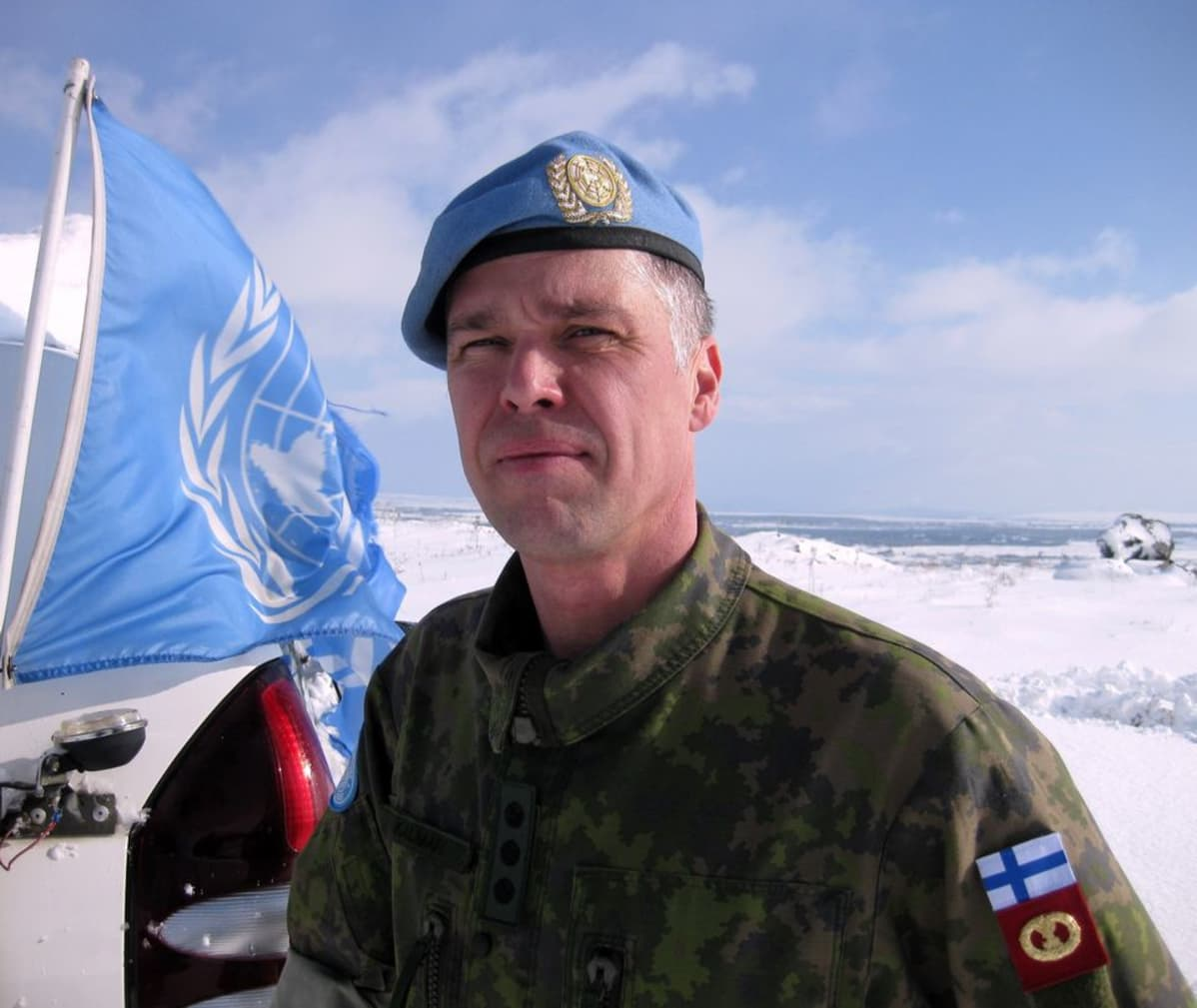 Liminkalainen Mika Kalvari valittiin vuoden 2015 rauhanturvaajaksi. Barettipäinen Kalmari seisoo YK:n lipun vieressä.