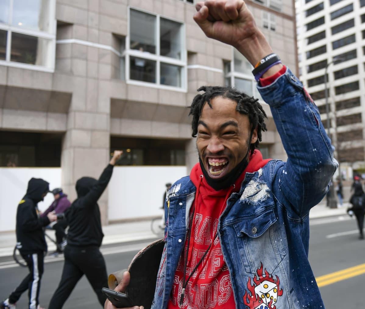 Mies iloitsi Minneapolisin oikeustalon ulkopuolella.