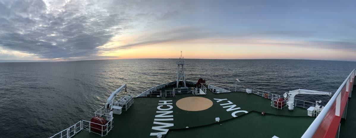 Laivan keula, edessä avovettä, horisontissa auringnlasku.