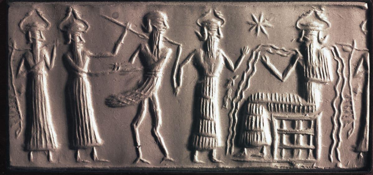Viisi pitkäpartaista, kypäräpäistä hahmoa, joista yksi istuu tuolissa ja muut seisovat hänen edessään.