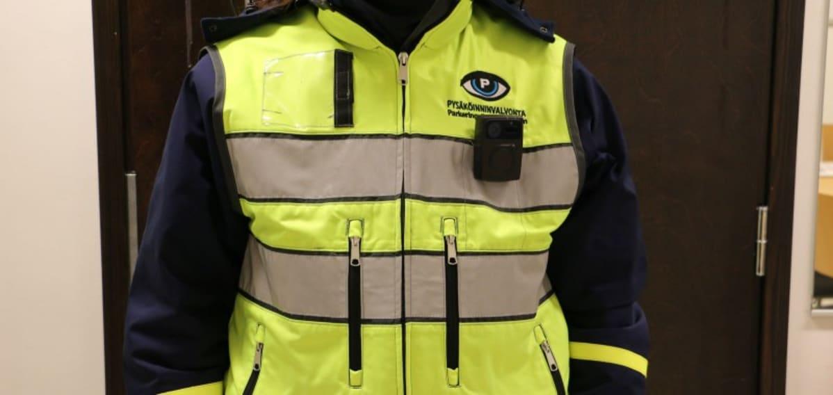 Pysäköinninvalvojan vaatteisiin on kiinnitetty pieni kamera.
