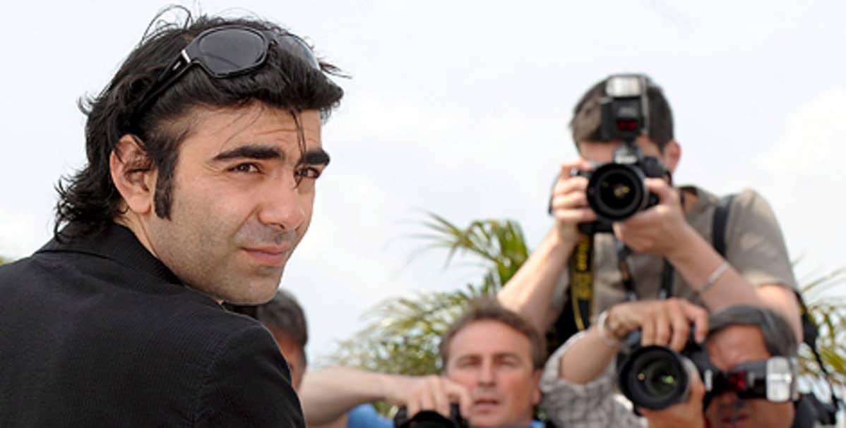 Fath Akin katsoo olkansa yli kameraan, takana joukko kuvaajia