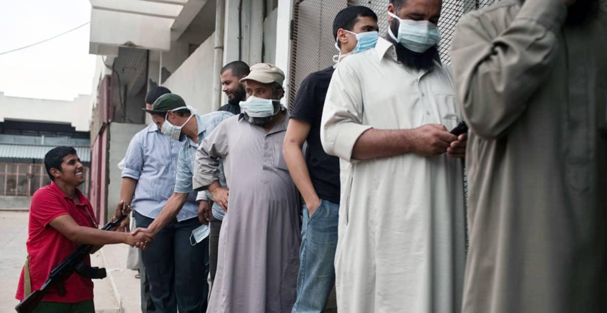 Libyalaiset jonottavat kadulla nähdäkseen Muammar Gaddafin ruumiin Misratassa.